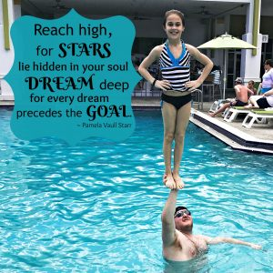 My daughter stunting in the pool with her coach. A quote on the page reads, Reach high for Stars...