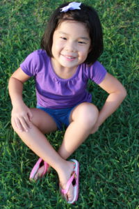 Lydia sitting in the grass, legs crossed with a big smile.